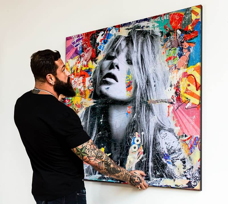 A man hanging large fabric pop art for the wall